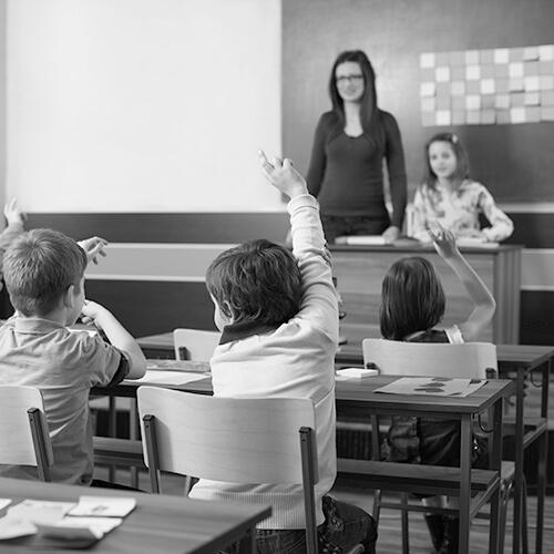 Children in elementary school are raised hand in clasroom